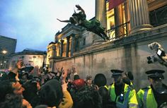 Chris Helgren   April 13, 2013. A reveller who had climbed onto a ledge outside the National Gallery leaps into the crowd during an outdoor party celebrating the death of former British Prime Minister Margaret Thatcher, at Trafalgar Square in central London.