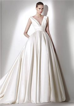 Princess wedding dress in mikado silk. Deep V-neck and draped sash. Square opening at the back. Wide skirt with gathers at the waist.