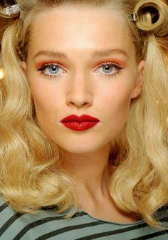 Pour Dior, les cheveux crantés et la bouche rouge rétro sont modernisés par un orange presque fluo sur les yeux.