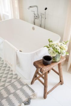 Freestanding bathtub accented with rustic saddle stool + gray and white patterned rug | Chango & Co.