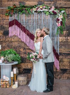 Yarn and String Wedding Decor with Major Wow Factor   This yarn wall decor is a total swoon fest! The vibrant colors of the yarn, adorned with clustering flowers on top, make for the perfect boho detail.