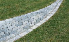 Bra lösning. Stödmuren kompletteras med en rad kantstenar i nivå med gräset. Kantstenarna underlättar när du klipper gräs samtidigt som de har en dekorativ effekt framför muren.