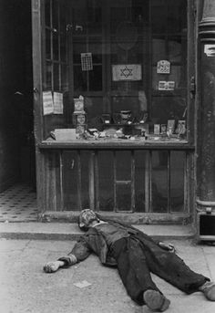 A Jewish occupant of the Warsaw Ghetto lies dead on the sidewalk in front of a small shop selling meager wares. As conditions in the ghetto worsened due to overcrowding, starvation and disease took a heavy toll on those forcibly interned there. Bodies of those who starved to death or died of disease were a common sight on the streets and sidewalks during the three year span from 1940 until 1943 that the Germans confined Jews to the ghetto. March 1941.