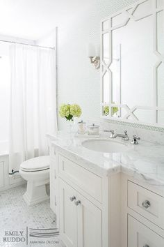 White and green bathroom features a wall clad in green trellis wallpaper, lined with a Worlds Away Vero White Lacquer Trellis Mirror over an extra wide single washstand topped with marble.