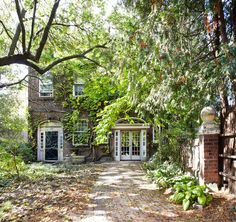 A stately older home, the facade covered in vines and the front walkway shaded by trees. Designed by http://stephanechamard.marklandhouse.com/index.htm