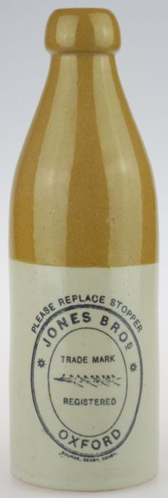 """Antique Bottles 298 - October - Berkhamsted Hertfordshire - There are eighteen or so varieties of printed stoneware ginger beer bottles known to have been used by Jones Brothers, some marked just Oxford and some Oxford and Reading. Of these there are five known variations of the larger, usually called 1 pint, bottles, all bearing the Rowing Eight trade mark. Standing 9.7"""" tall this particular example was manufactured by Bourne of Denby and bears both their printed and impressed marks."""