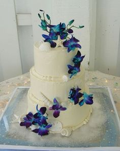 Beach themed cake with blue orchids to match the bouquet. seashells & starfish on cake edging