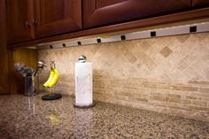 Angle power strip under kitchen cabinet | Hidden, convenient access to electrical outlets without disrupting the pattern of the backsplash tiles.