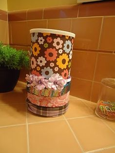 A Quaker oats tin covered with decorative paper to use as a headband organizer with room for bows or hair bands inside