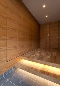 木目が美しい玄関ホール。足元は柔らかな間接照明で高級料亭へ足を踏み入れたよう。大容量の玄関収納は、木目の壁と一体化し、収納とは気づかない、すっきりとした美しい仕上げになっています。