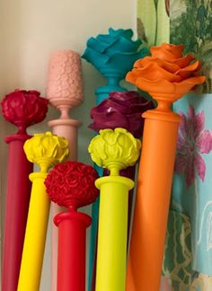 DIY Paint Curtain Rods Bright Primary Colors.. also look for door knobs and other funky knicknacks as finials.. BUT don't attach the finials until AFTER you paint it all or your curtain rod is glued together w/o your curtains :/