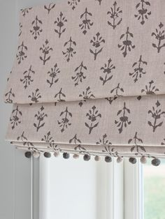 This Charcoal Moonflower Linen in a roman blind with light beech charcoal pompoms is classic yet contemporary. A delicate floral print with colours inspired by an old Indian mural. This versatile design with a small pattern repeat is perfect for curtains, blinds and upholstery.