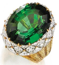 18 Karat Two-Color Gold, Tourmaline and Diamond Ring, Buccellati, 1975  Estimate: 18,000 - 22,000 USD  Centered by an oval tourmaline weighing 29.90 carats, framed by numerous round and old European-cut diamonds weighing 2.32 carats, size 7, signed Buccellati Italy. With signed box. Sotheby's.