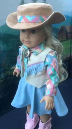 This five piece western outfit is for the little cowgirl in your family. The cotton shirt has a western inspired pink and blue print, and is long sleeved with cuffs fastened with a Velcro closure. At the neck is a silver Concho threaded with a rawhide tie. The vest is made of felt, and finished with blue knit fringe embellished with embroidery. The full skirt is made of a blue knit fabric, with a waistband and Velcro closure. The handmade faux suede cowboy hat has a coordinating decorative…