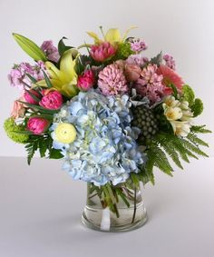 Morning Breeze - A lovely assortment of spring flowers in soft pastel colors is arranged in a glass vase. Included are hydrangea, tulips, hyacinth, stock and more. #KittelbergerFlorist #RochesterFlowers