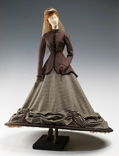 """1855 Doll""  with costume designed by Véra Boréa in1949 as part of the Friendship Train. ""The unique style of this dress was taken from one launched by Empress Eugénie during her trips to the Pyrenees Mountains. The skirt is lopped up by tabs from the underskirt. The shoes are particular highlights of this ensemble, featuring incredible detail."