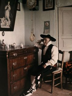 A Segovian wine merchant in Castilian costume sits in a chair. Segovia, Spain. Gervais Courtellemont. National Geographic before 1924