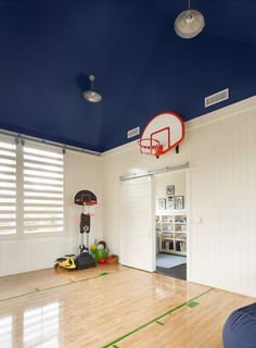 Fun boy's playroom basketball court with painted blue ceiling, sliding door on rail, glossy wood basketball floors, red basketball hoop and blue poufs.