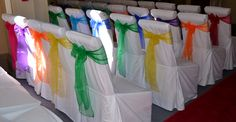 A very colourful rainbow wedding with mixed rainbow coloured organza bows on white chair covers. The Sophisticated Touch ...Chair Covers by Design
