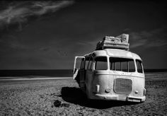 Beached Bus Wall Mural: Nature: Beach: A black and white seascape pictures an abandoned bus on the sandy beach. Suitcases fill the luggage racks, leaving hope for returning passengers. A minimalistic wall mural image that can be printed on demand. Your specifications will be met for any interior design or home decor project. Create your own wallpapers, wall art and more by exploring our extensive collections.