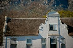 The iconic crisp, white, delicately detailed Cape Dutch architecture of South Africa stands so beautifully against nature's backdrop. Cape Dutch, Thatched Roof, Wines, South Africa, Holland, Backdrops, Exterior, Mansions, Landscape