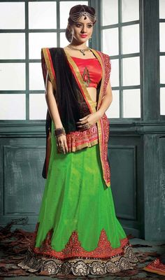 Lime green georgette lehenga with contrast choli and dupatta makes perfect combo any festive season party. The lehenga is embellished with woven lace and silk thread embroidered decorative cut work border with sprinkled crystal stones which gives you an grand and exquisite look. The contrast black net dupatta is embellished with woven lace and silk thread embroidered border. The lehenga comes with contrast red raw silk stitched blouse as shown in the picture. #IndianLehengaCholi