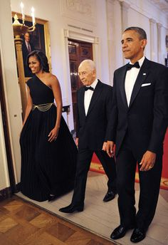 I LOVE this dress on Mrs. Obama!  The black chain belt adds a sexy sophisticated edge that takes it from a simple Black Grecian Dress to the next level!  I wonder who the designer is?