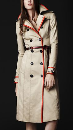 Burberry's Stretch Gaberdine Trench... £ 1,995.00   Knee-length trench coat in innovative lightweight stretch cotton gabardine  Brightly coloured textured leather trim  Feminine fit with tapered sleeves and lightly padded shoulders  Heritage epaulettes,two gun flaps, belted cuffs  Hook-and-eye collar closure, slanted pockets, back rain shield and central back pleat  Authentic leather buckles  Horn buttons engraved with the Burberry logo  A Fabric belt is supplied with the coat