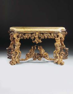 A VENETIAN CARVED BOXWOOD AND WALNUT SIDE TABLE - Circle of Andrea Brustolon, early 18th Century - A foliate & floral entwined moulding frame, & deeply carved pierced frieze with fruit, flowers & scrolls centred by a cherub, supported by two satyres at the front supporting monster heads & two draped men at the back, standing on dragons, joined by a central stretcher carved with two female figures each with one hand raised,   35 in. high; 69¾ in. wide; 31 in. deep