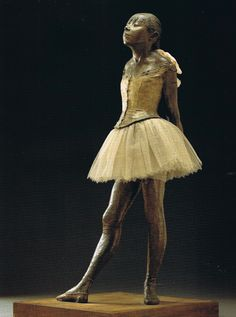 """The """"Little Dancer of Fourteen Years"""" (""""French: La Petite Danseuse de Quatorze Ans""""), one of Degas' most famous sculptures, was originally done in wax during c. 1881, and not cast in bronze until 1922. It is dressed in a cotton skirt and with a hair ribbon."""