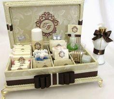 Caixa de madeira forrada de tecido adamascado marfim, com divisórias. Com bordado na tampa. Incluso itens de higiene e medicamentos com rótulos personalizados. Incluso 1 sabonete líquido decorado combinando com a decoração da caixa. Tamanho 33x25cm R$ 384,00: