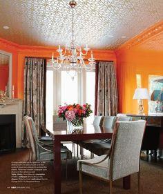 Sala de jantar com parede laranja.
