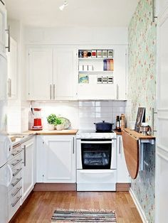 Litet men bedårande kök, och framför allt smarta lösningar. Notera det väggfasta klaffbordet som både kan användas som extra arbetsyta och som matplats. Fälls dessutom ner vid behov av större plats i köket. Detaljen med en tapetserad fondvägg ger köket karaktär. – Sköna hem