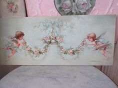 THIS IS CALLED CUPID GARLAND. At the ends are a precious cherub and cupid with wings by Christie Repasy