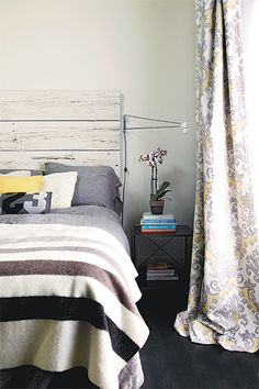 grey,white and yellow, modern country style bedroom is stripped of fussy details, has modern/industrial touches like the light mix with trad items like Hudson Bay point blanket in grey strip on bed, floral or scroll pattern curtains