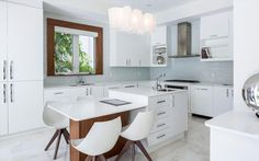 A white modern kitchen with a light gray glass mosaic tile backsplash and a small island that serves as a in-kitchen eating area and as extra countertop and storage space. Kitchen Island With Table Attached, Kitchen Island Designs With Seating, Kitchen Island Lighting Modern, Kitchen Island With Seating, Island Kitchen, Island Sinks, Kitchen Counters, Kitchen Designs, Luxury Kitchens