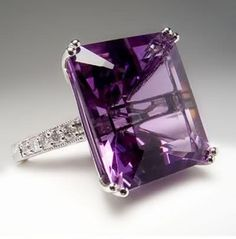 This natural amethyst cocktail ring features a massive 13 carat emerald cut center stone with natural diamond accents.