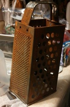 DIY Primitive cheese grater... put  vinegar and regular salt in a glass baking dish over several days flipping often as you see a lot of rust  finish in the dishwasher you can also do vinegar salt and peroxide there you have a rusted grater...