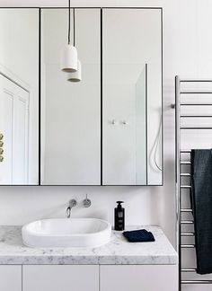 This bathroom features ample storage in white cabinetry and behind the mirrors. A porcelain pendant light hangs above the marble benchtop and complements the white partially inset basin. Interior Design Awards, Bathroom Interior Design, Modern Interior, Bathroom Designs, Bad Inspiration, Bathroom Inspiration, Steel Frame Doors, Villa, Modern Bathroom