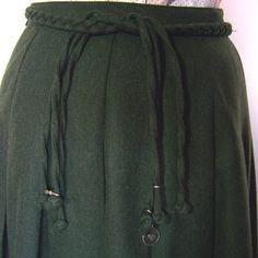 Sehr schöner Faltenrock aus grünem Wollstoff, komplett gefüttert.  Der hübsche Gürtel aus geflochtenem Loden gehört dazu. Verschließbar ist er seitlich mit Reißverschluss.  Der Rock ist kaum...