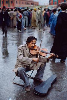 Todo está mojado, nadie hace caso, pero él... sigue tocando su violín. Os imagináis la canción??