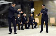 Japan's Prime Minister Shinzo Abe receives a rugby ball from member of Japan's national team Ayumu Goromaru (L) during a courtesy call by national team members at Abe's official residence in Tokyo, October 21, 2015. in the background are (seated R to L) Honorary President of the Japan Rugby Football Union Yolshiro Mori, President of the Japan Rugby Football Union Tadashi Okamura and executive of the Japan Rugby Football Union Noriyuki Sakamoto. REUTERS/Toru Yamanaka/Pool