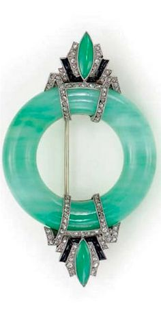 AN ART DECO JADEITE, DIAMOND, ONYX AND PLATINUM BROOCH  Jadeite, mottled green hue, light to medium tone, numerous rose-cut diamonds, bright and lively, onyx intact, circa 1930, with French assay marks, shows signs of normal wear