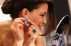 A model at Sotheby's auction house wears emerald and diamond earclips and an emerald and diamond ring from the collection of actress Gina Lollobrigida, which are each expected to fetch £163,000 and £117,000 respectively