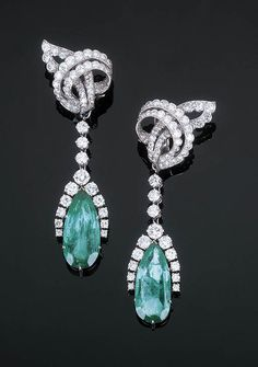 A Pair of Diamond Ear Clips with Emerald Pendants   Each comprising a detachable pear-shaped emerald pendant weigh 11.93 and 8.78 carats with a circular-cut diamond border to the diamond line suspended from the scrolled openwork circular-cut diamond surmount, with a red leather case, with French assay and maker's marks, 6.5 cm long  The ear clips only signed Cartier, Paris, No's R2562 and 01933