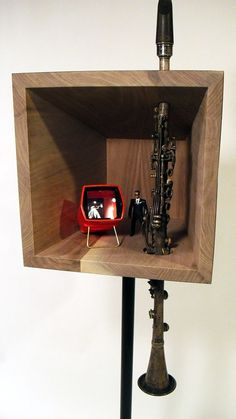 "Fo Wilson, untitled (#3), 2013 Walnut, steel, found French clarinet, Will Smith action figure, gaf anscochrome slide viewer, 35mm photo of Miles Davis (Francis Wolff, 1954). 44""h x 12"" w x 13""d. a well-worn instrument and an image of the jazz innovator Miles Davis speaks to black male heroism and the miscegenation of cultures –  an aspect of African identity that is central to African American creative expression as in jazz, hip-hop, colloquial language and other aspects of popular culture."
