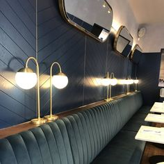 Green Velvet Banquette Seating | Chevron Herringbone Wood Panelling | Brass Mirrors + Lighting