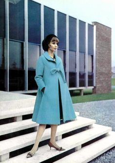 Model in wonderful blue wool coat, tied with bow, narrow at shoulders, widening at the bottom, by Nina Ricci, shoes by Charles Jourdan, photo by Pottier, 1963