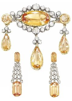A 19TH CENTURY TOPAZ AND DIAMOND DEMI-PARURE. Comprising a pair of earrings of tapering form, the topaz tops each suspending an old-cut diamond pierced panel of stylised curling foliate motifs, to articulated topaz drops, together with a brooch of girandole form, the central oval mixed cut topaz and old-cut diamond cluster suspending three articulated topaz drops each with diamond trefoil surmount, mounted in silver and gold. #19thCentury #antique #brooch #earrings