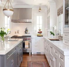 narrow windows next to range,  gray island base, white counters, white cabinets
